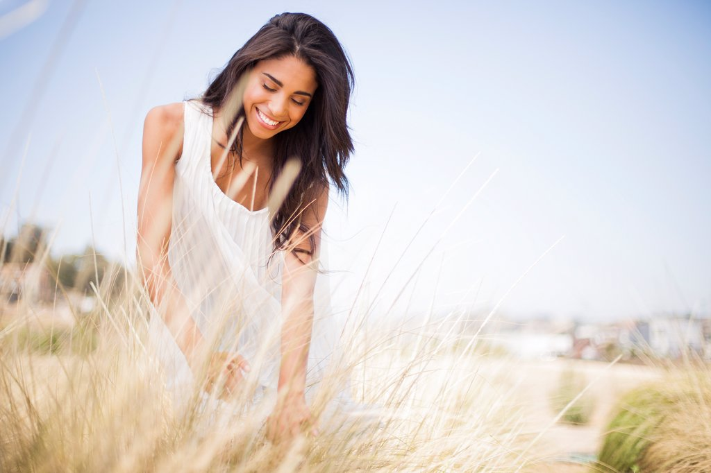 Stock Photo: 4278-9605 Smiling Woman in a Field of Tall Grass