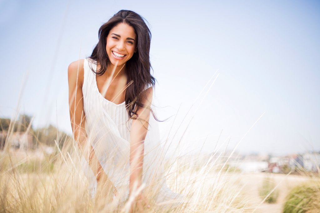 Smiling Woman in a Field of Tall Grass : Stock Photo
