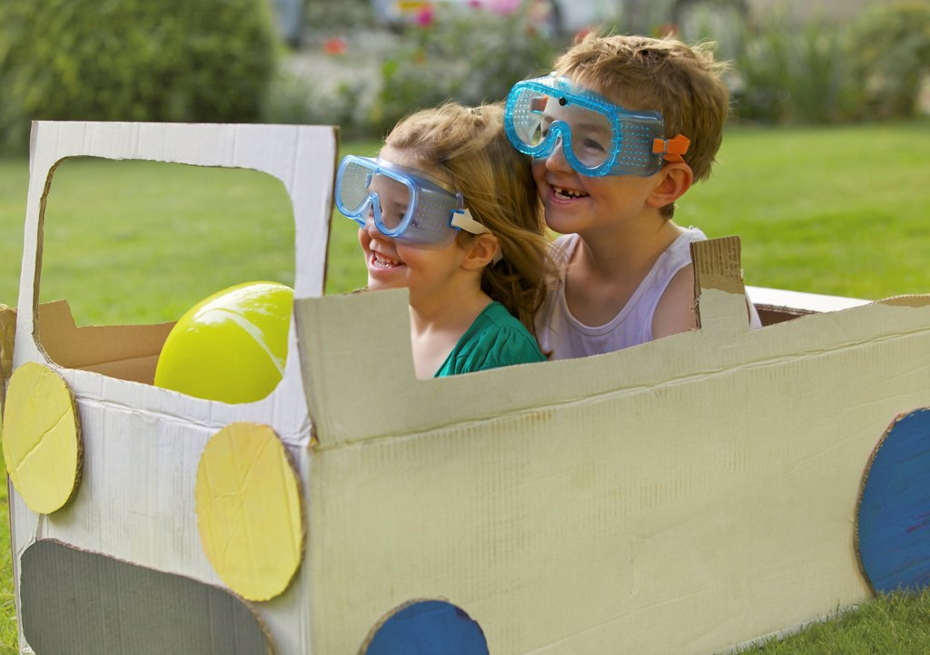 Boy and Girl Wearing Goggles Driving Cardboard Car : Stock Photo