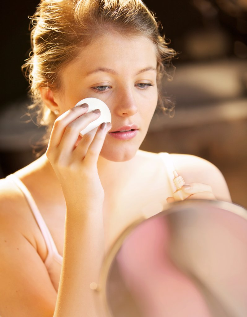 Young Woman Applying Makeup with Cotton Pad : Stock Photo
