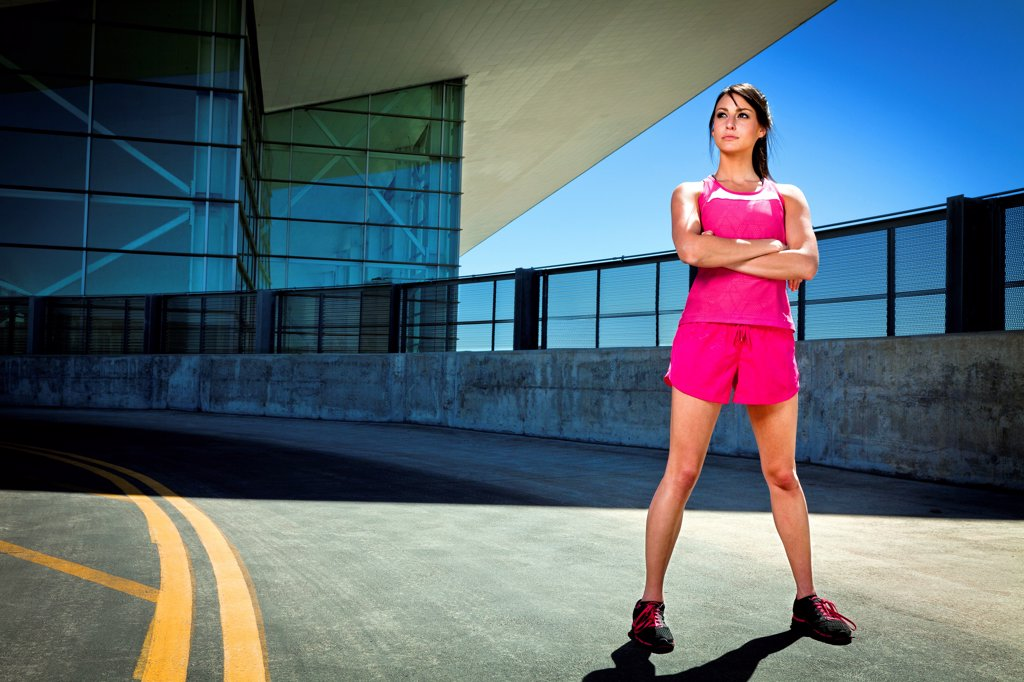 Young Woman in Sportswear Standing with Arms Crossed : Stock Photo