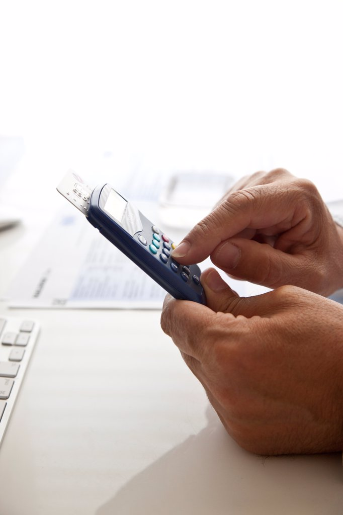 Stock Photo: 4278-9631 Man's Hands Typing into a Banking Card Reader