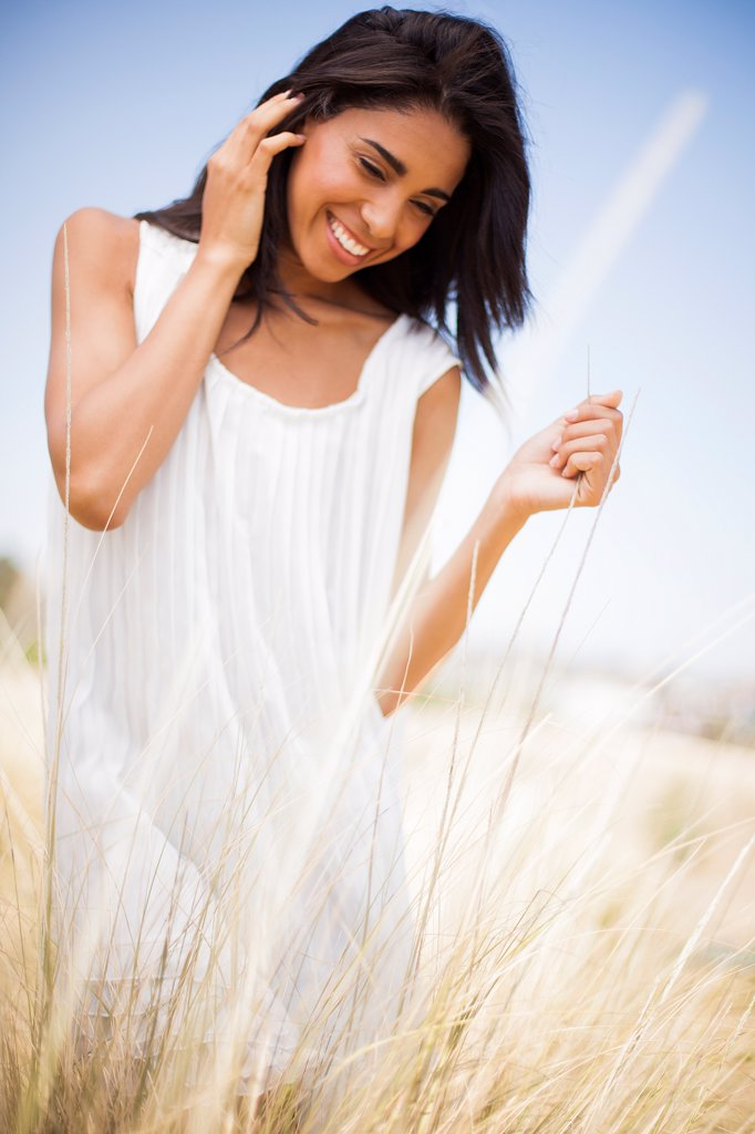 Stock Photo: 4278-9632 Smiling Woman in a Field of Tall Grass