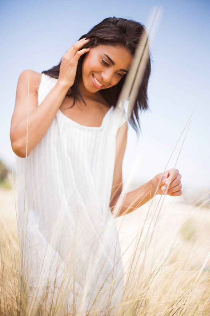 Stock Photo: 4278-9633 Smiling Woman in a Field of Tall Grass
