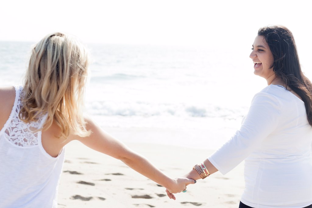 Two Women Holding Hands on a Beach : Stock Photo