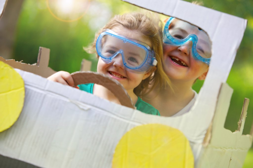 Stock Photo: 4278-9649 Boy and Girl Wearing Goggles Driving Cardboard Car
