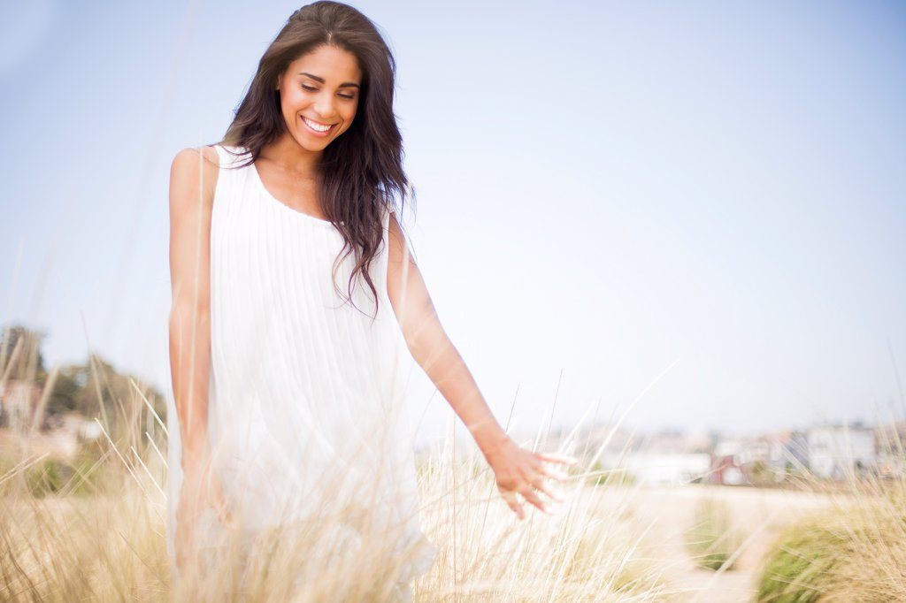 Stock Photo: 4278-9652 Smiling Woman in a Field of Tall Grass