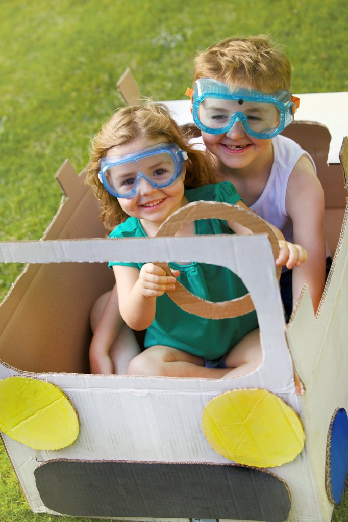 Stock Photo: 4278-9684 Boy and Girl Wearing Goggles Driving Cardboard Car