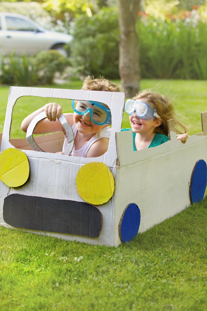 Stock Photo: 4278-9728 Boy and Girl Wearing Goggles Driving Cardboard Car
