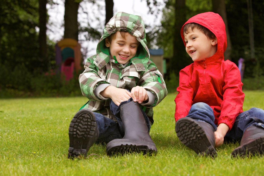 Two Boys Putting on Wellington Boots Outdoors : Stock Photo