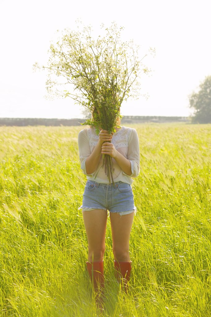 Stock Photo: 4278-9764 Woman Standing in a Field Holding a Bunch of Wildflowers in front of her Face