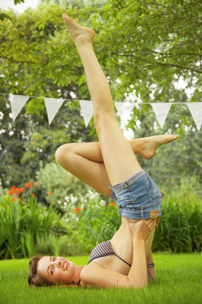 Teenage Girl Doing Shoulder Stand in Garden : Stock Photo