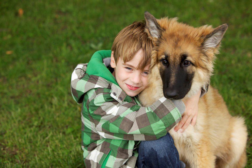 Boy Hugging Alsatian Puppy : Stock Photo