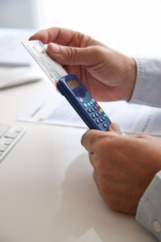 Stock Photo: 4278-9806 Man's Hands Inserting Credit Card into a Card Reader