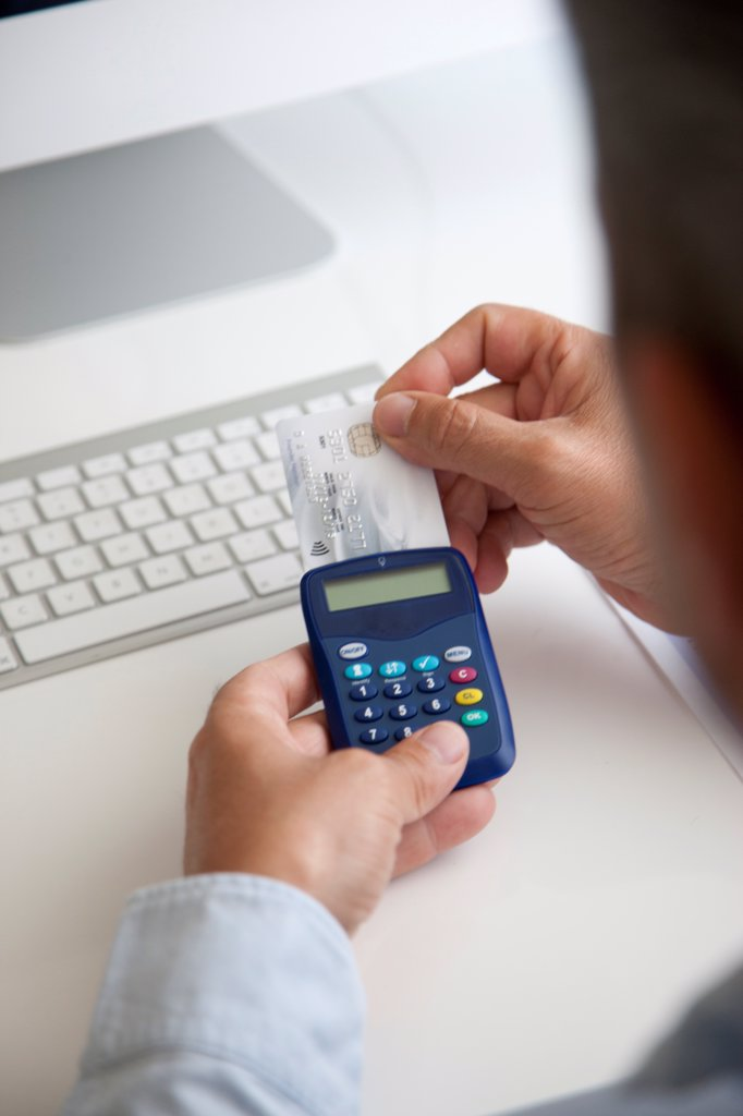 Stock Photo: 4278-9807 Man Inserting Credit Card into a Card Reader