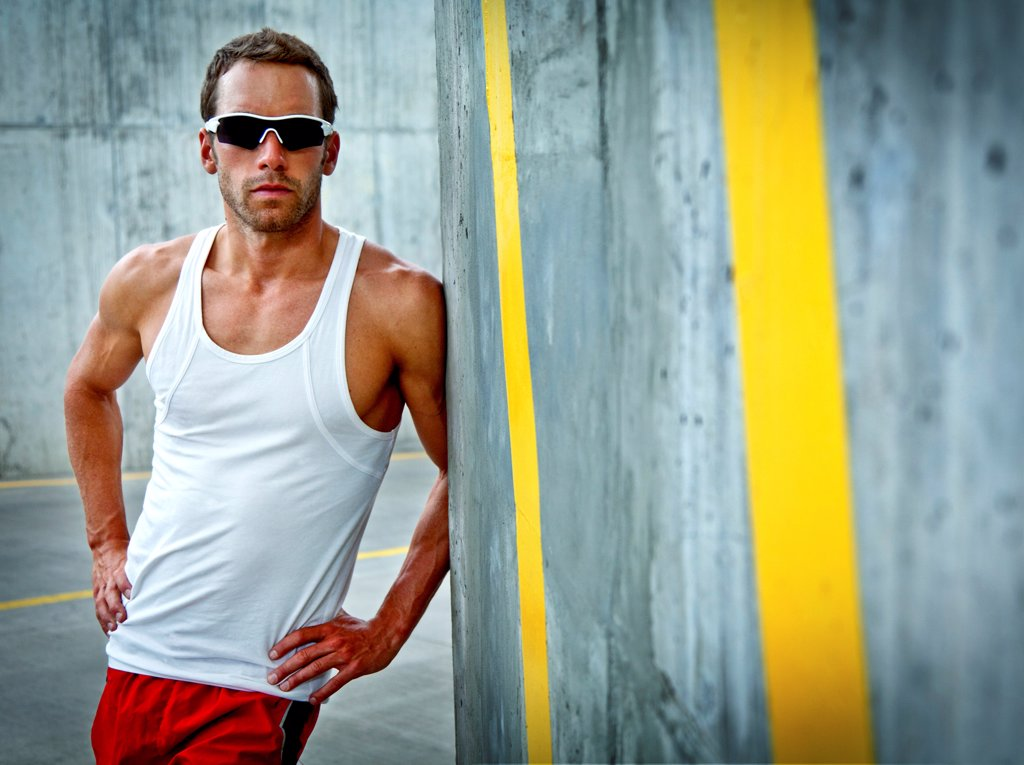 Stock Photo: 4278-9812 Sportsman Leaning against Concrete Wall