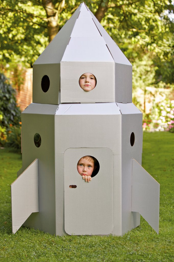 Stock Photo: 4278-9824 Two Boys Looking Out from Window of Cardboard Rocket Spacecraft
