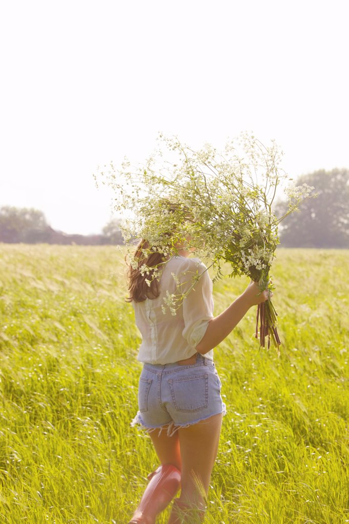 Back View of Young Woman in a Field Holding a Bunch of Wildflowers : Stock Photo