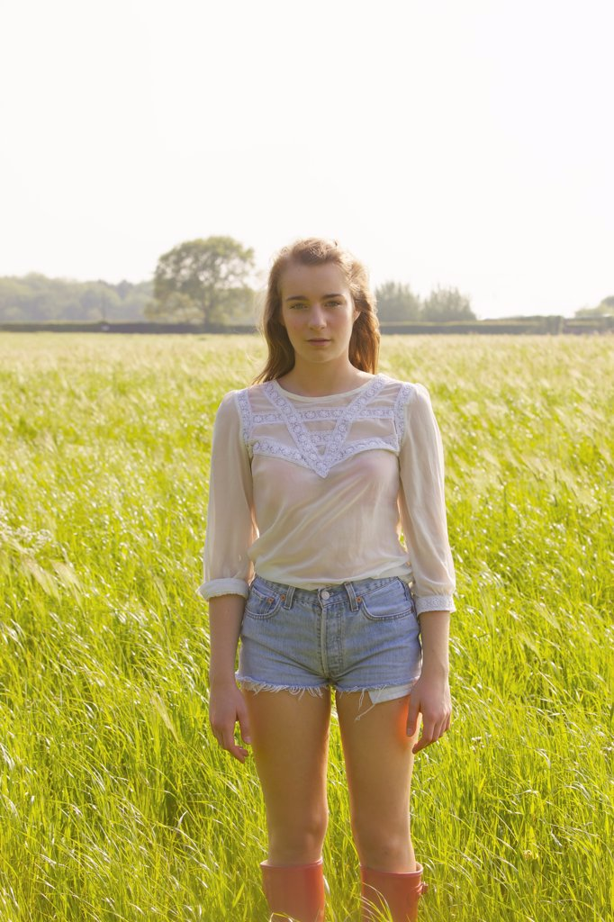Young Woman Standing in a Field : Stock Photo