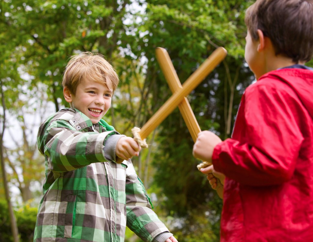 Two Boys Playing at Sword Fighting : Stock Photo