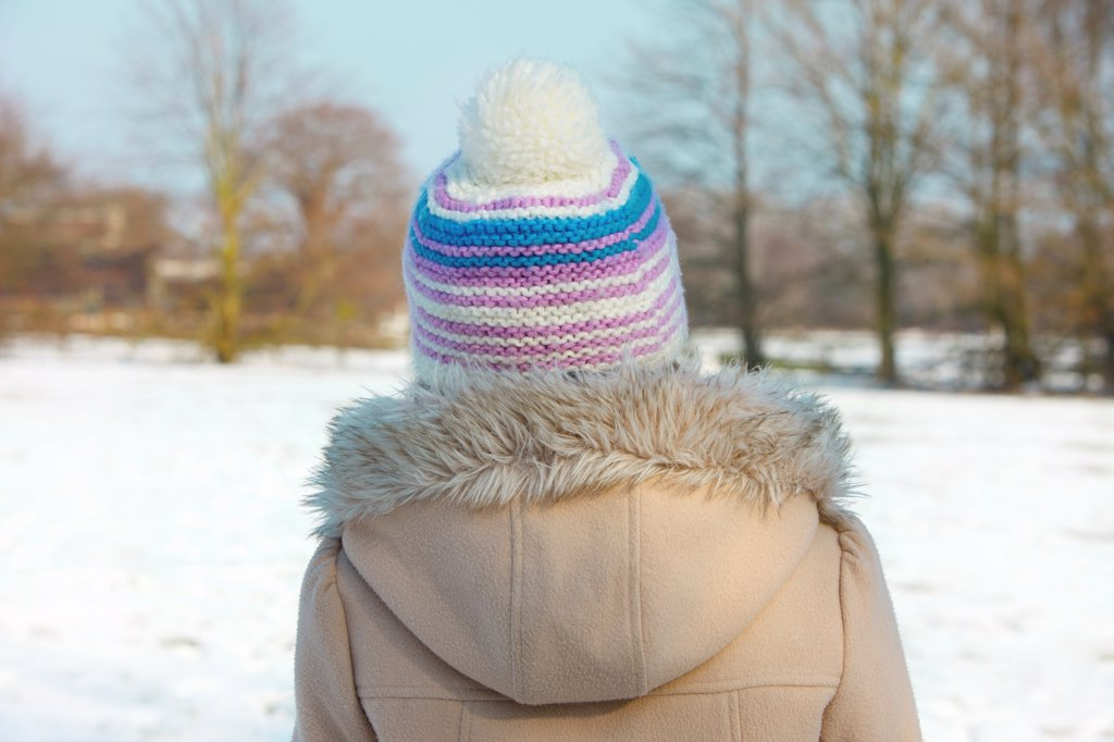 Stock Photo: 4278-9859 Back View of Girl in a Parka and Wool Hat Outdoors