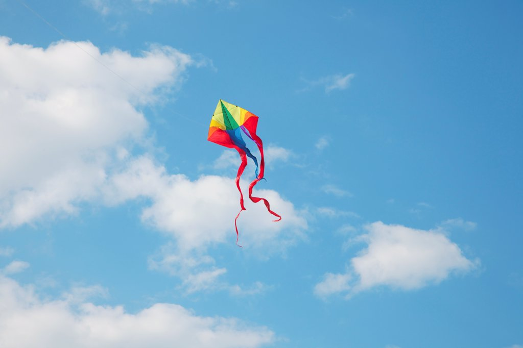 Stock Photo: 4278-9864 A Kite Flying in a Cloudy Blue Sky