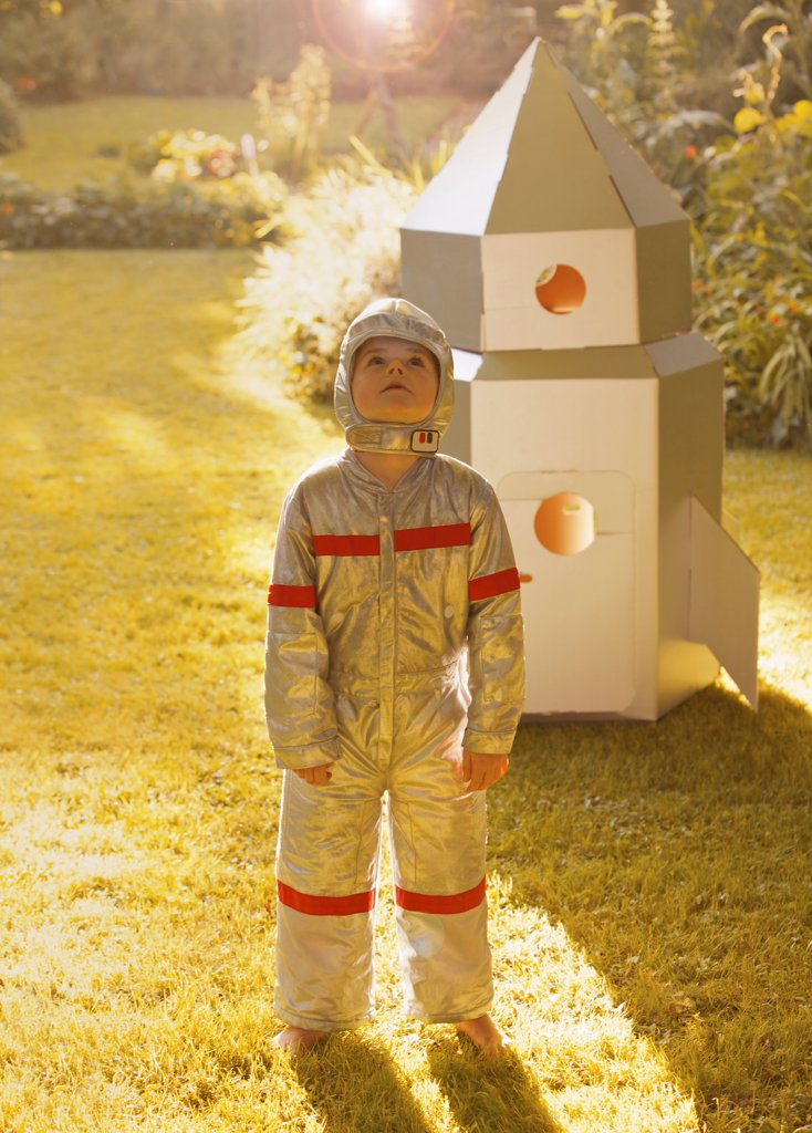 Boy Wearing Space Suit Standing in front of Cardboard Rocket Spacecraft : Stock Photo