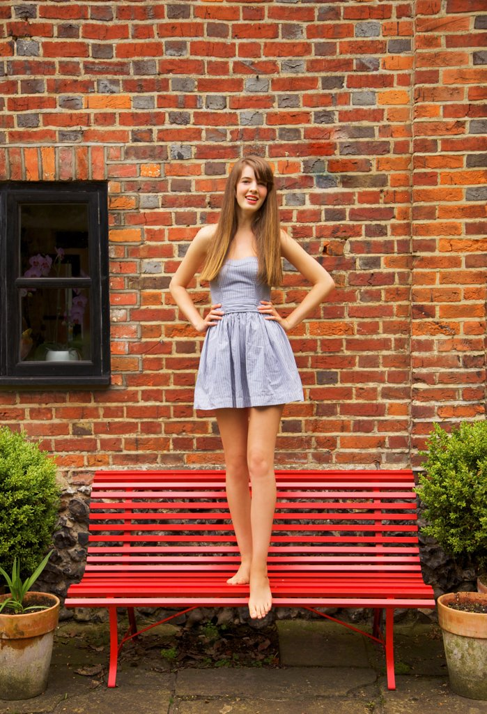 Teenage Girl Standing on Red Bench : Stock Photo