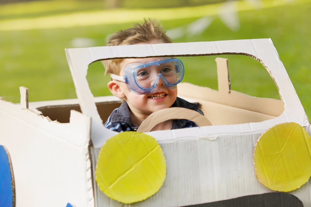 Boy Wearing Goggles Driving Cardboard Car : Stock Photo