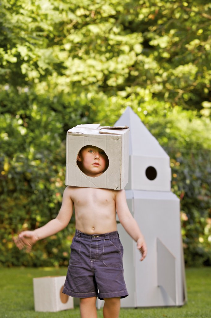Stock Photo: 4278-9909 Boy Wearing Homemade Cardboard Helmet Playing in front of Rocket Spacecraft
