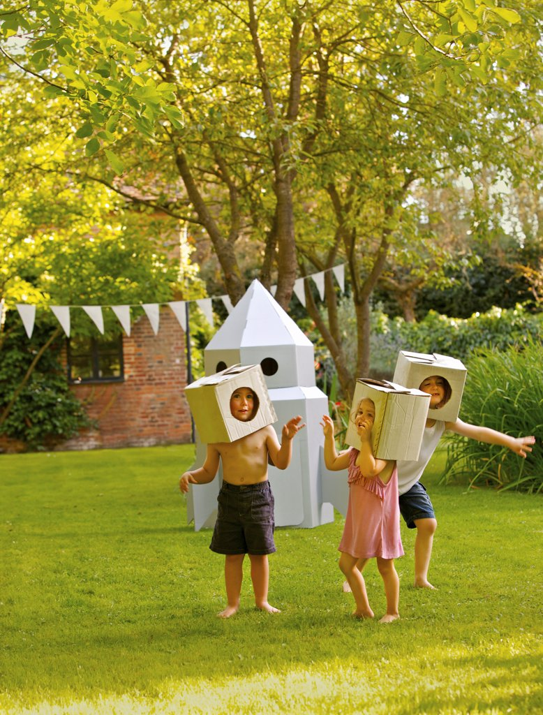Stock Photo: 4278-9921 Children Wearing Homemade Cardboard Helmets Playing around Rocket Spacecraft