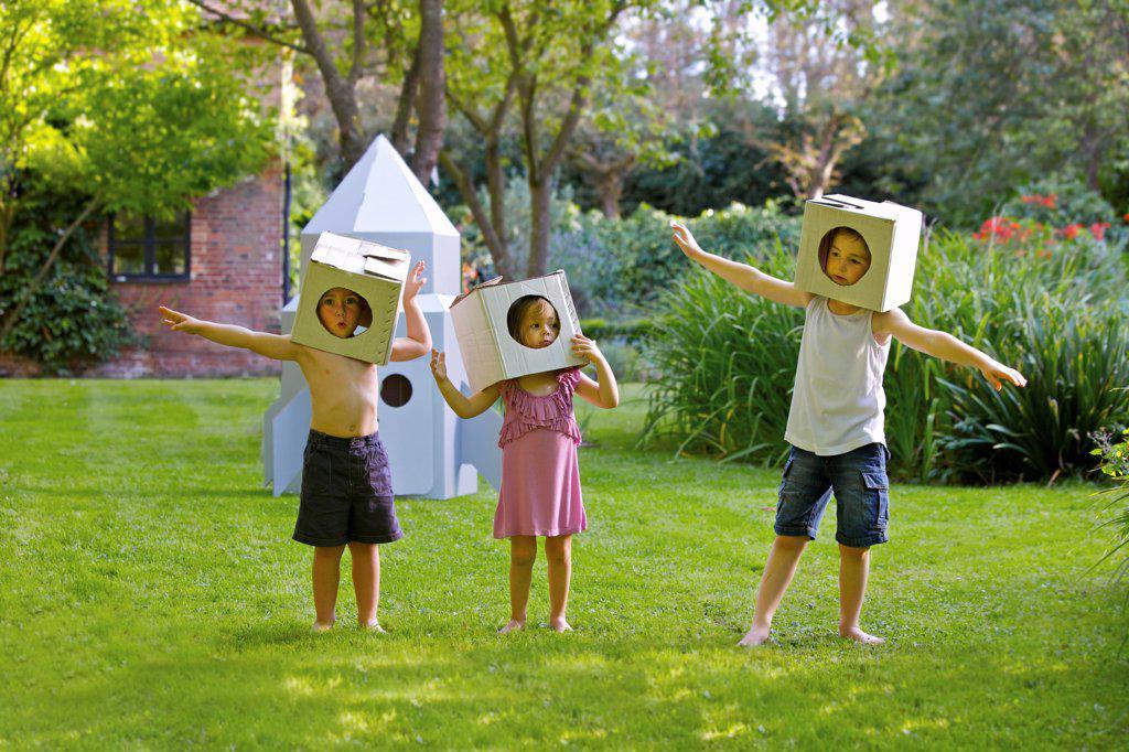 Stock Photo: 4278-9937 Children Wearing Homemade Cardboard Helmets Playing around Rocket Spacecraft