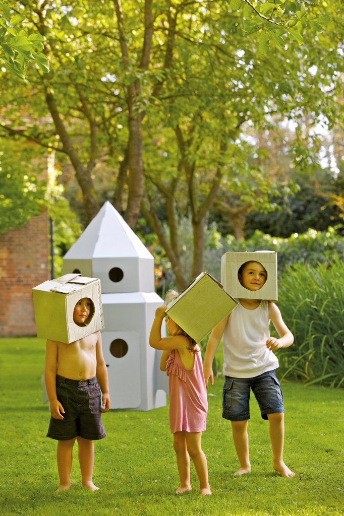 Children Wearing Homemade Cardboard Helmets Playing around Rocket Spacecraft : Stock Photo