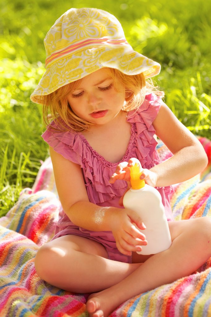 Stock Photo: 4278-9973 Young Girl Applying Suntan Lotion on Arm