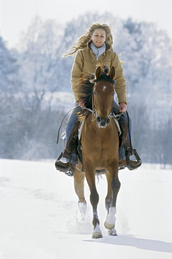 Stock Photo: 4279-24141 Young lady riding western-style on back of an Arabian horse at winter