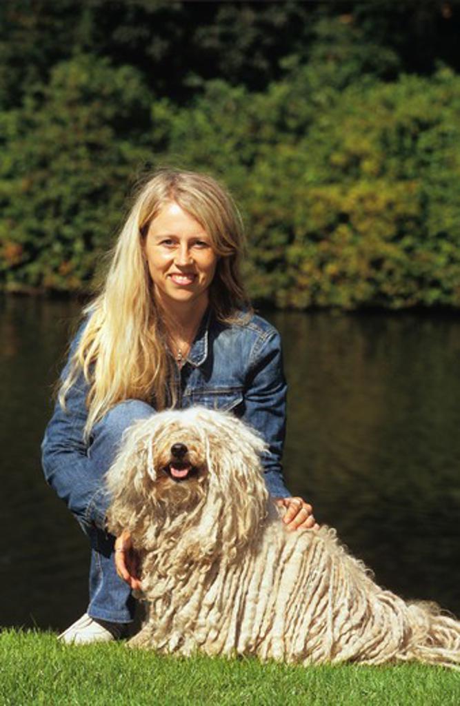 puli dog lying on meadow beside a woman : Stock Photo