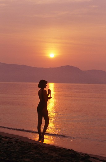 Stock Photo: 4279R-47841 woman - standing in water - sunset