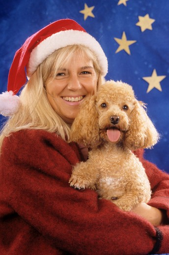 Stock Photo: 4279R-48244 woman with poodle in front of christmas decoration