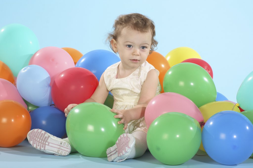 little girl sitting in between balloons : Stock Photo
