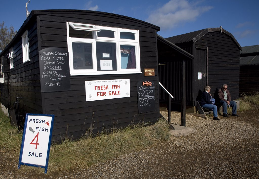 Stock Photo: 4282-10315 England, Suffolk, Orford. A man and woman sitting outside Brinkleys Shed offering fresh fish for sale in Orford.