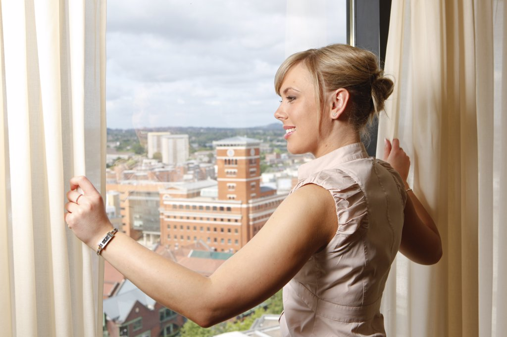 Stock Photo: 4282-10479 England, West Midlands, Birmingham. Woman in a hotel suite pulling back the curtains to look out over the city of Birmingham.