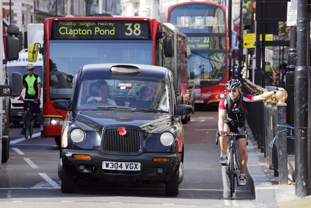 Stock Photo: 4282-11563 England, London, Piccadilly. Cyclists, busses and taxis waiting at traffic lights in Piccadilly.