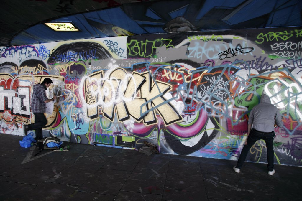 Stock Photo: 4282-11595 England, London, South Bank. Graffiti artists at work in an area known as the under-croft on the South Bank in London.