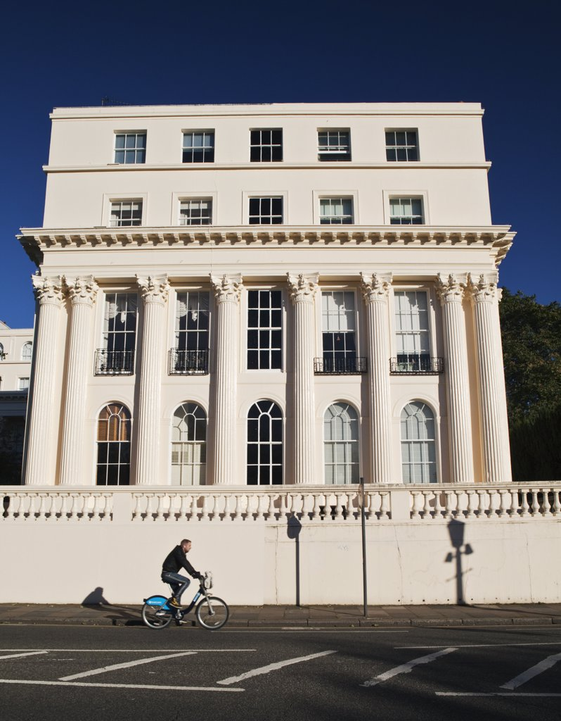 Stock Photo: 4282-11779 England, London, Regent's Park. A man cycling using a 'Boris Bike' past a 19th century stuccoed building designed by architect John Nash in Cumberland Terrace.