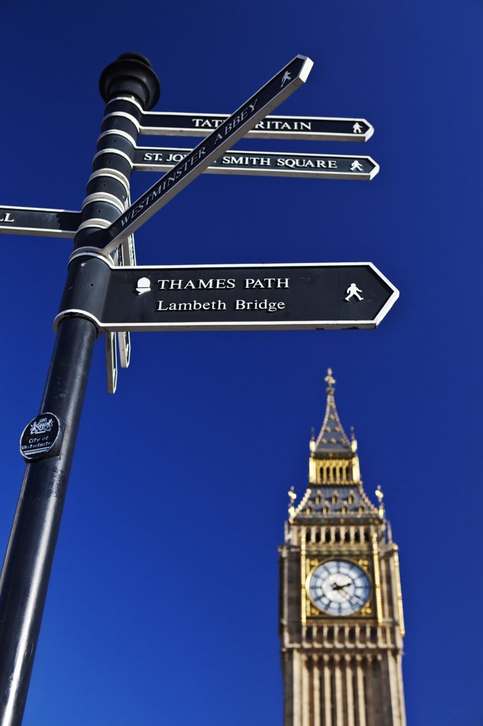 Stock Photo: 4282-11784 England, London, Westminster. Big Ben towering over a directional signpost pointing the way to the nearby tourist attractions.