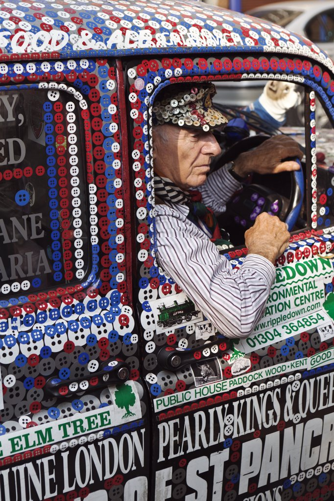 England, London, Greenwich. A taxi driver in a Pearly Kings and Queens decorated London taxi cab. : Stock Photo
