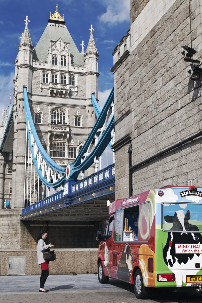 England, London, Tower Bridge. A woman approaching an ice cream van parked next to Tower Bridge. : Stock Photo