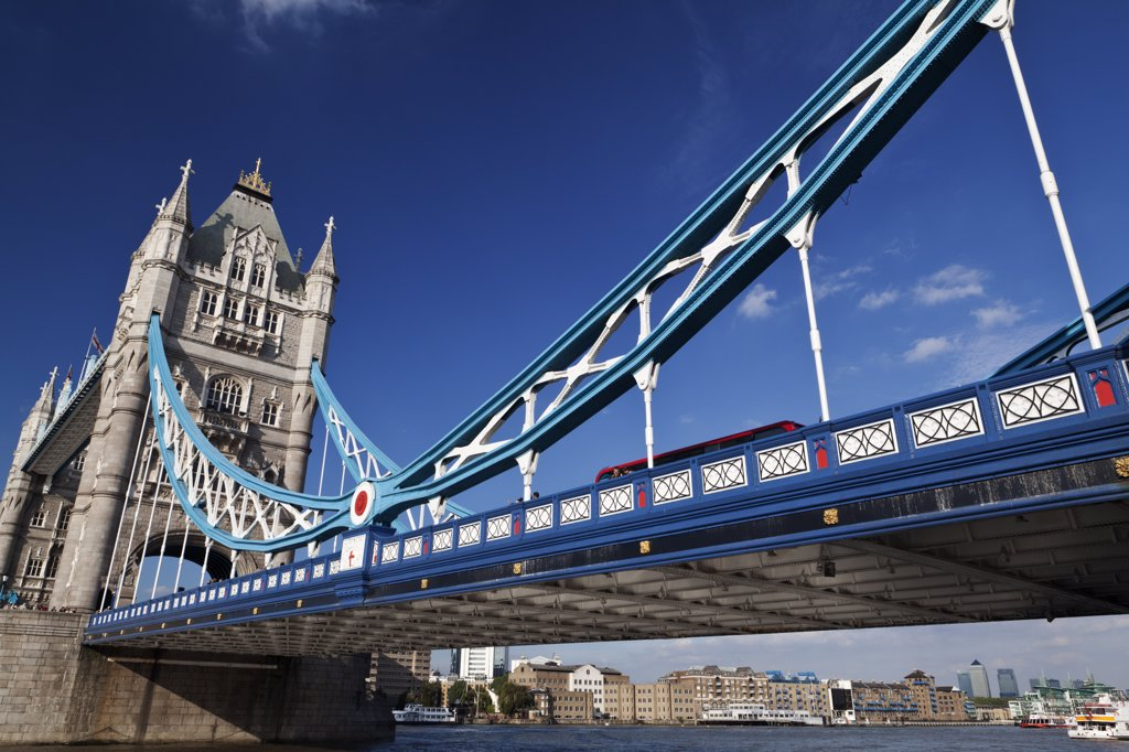 England, London, Tower Bridge. A red London bus crossing the River Thames over Tower Bridge, one of London's most famous and iconic landmarks. : Stock Photo