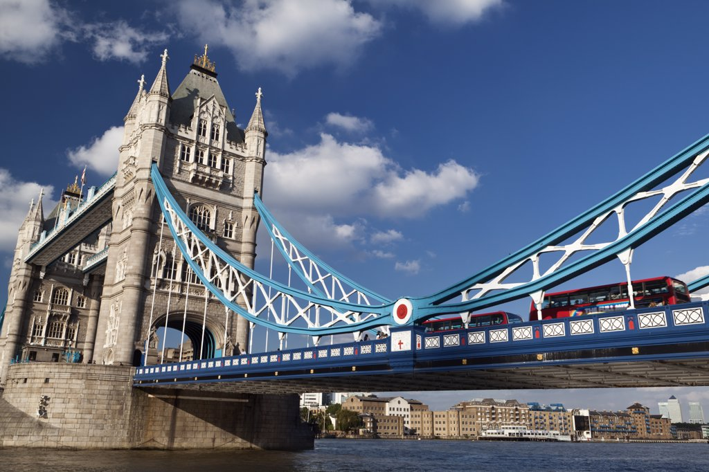 England, London, Tower Bridge. Red London buses crossing the River Thames over Tower Bridge, one of London's most famous and iconic landmarks. : Stock Photo