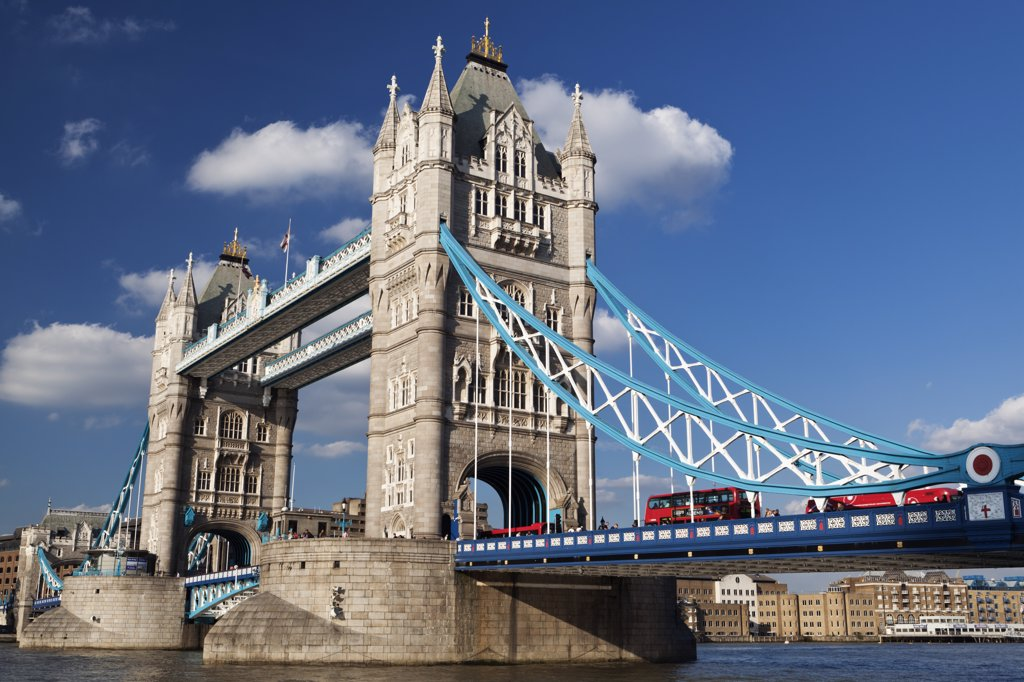 Stock Photo: 4282-12003 England, London, Tower Bridge. Red London buses crossing the River Thames over Tower Bridge, one of London's most famous and iconic landmarks.